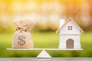 House and cash on a balance scale