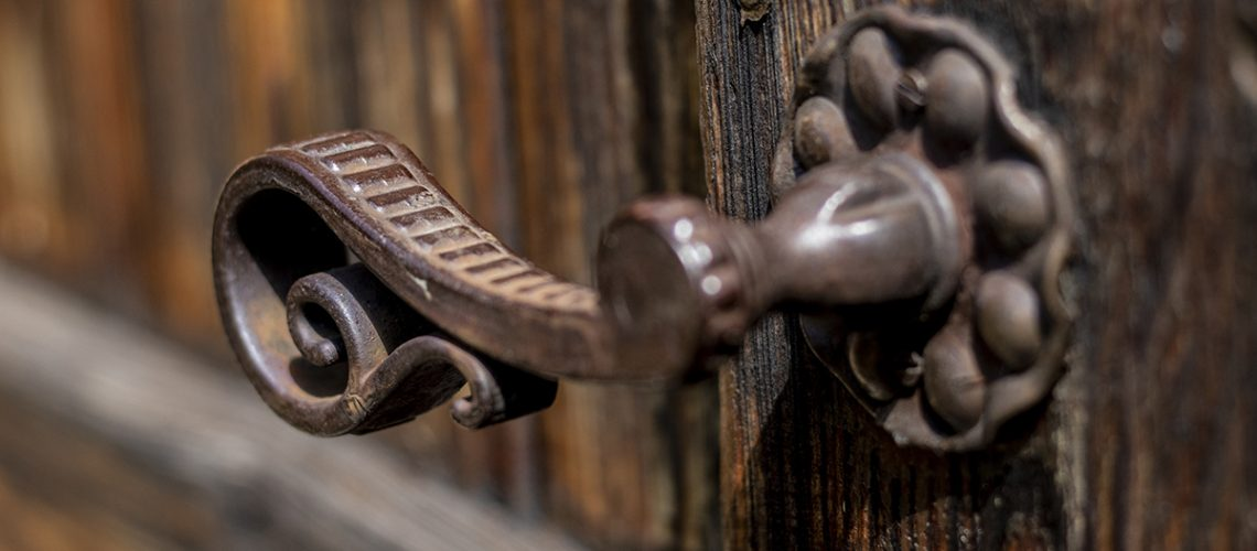 Old metal - iron, handle on a wooden door.