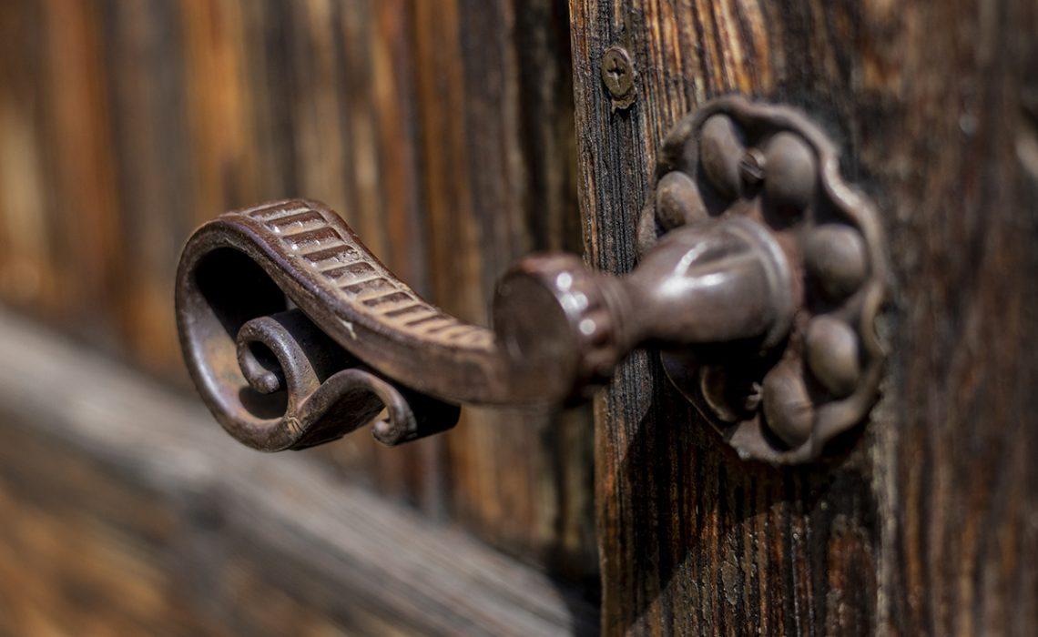Old metal - iron, handle on a wooden door.